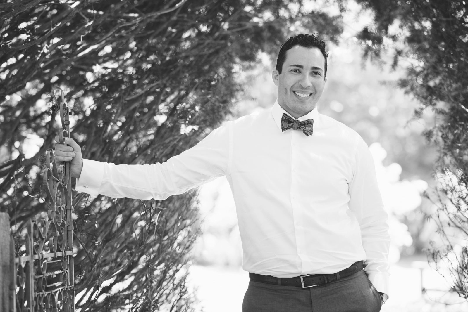 black and white casual portrait of groom standing under archway at Mass Audubon's Sanctuary