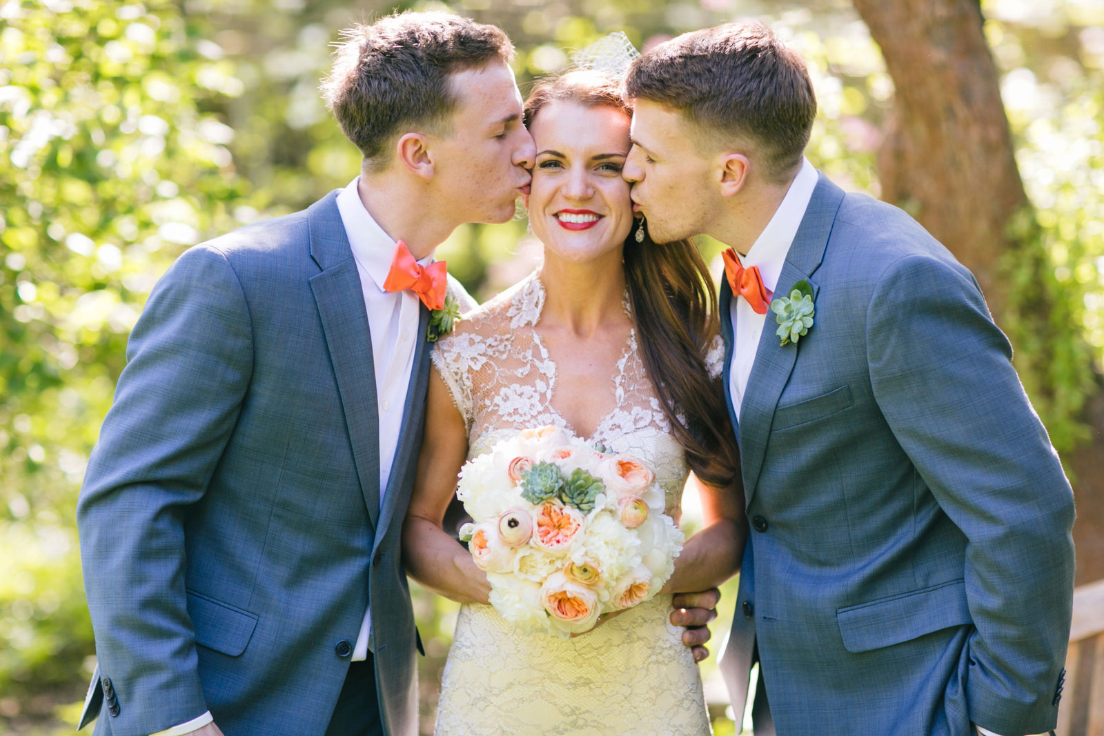 brothers of the bride kissing bride on the cheek during casual family portrait session