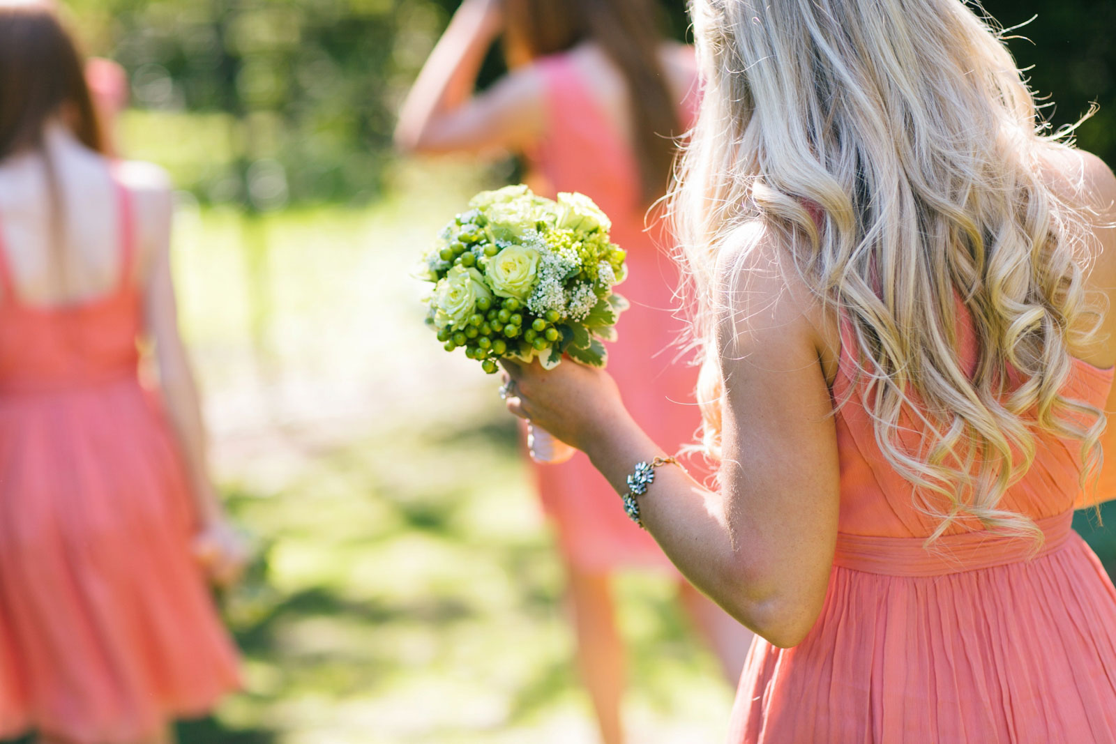 bridesmaid holding bouquet with green roses, baby's breath, and green berries