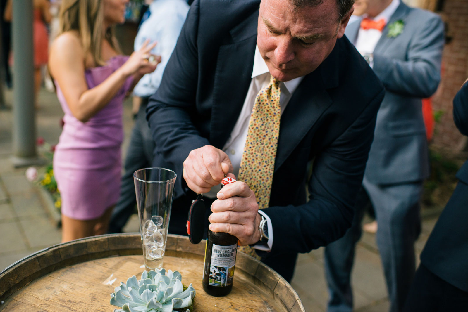 wedding guest opening a Harpoon beer at outdoor spring wedding in Boston