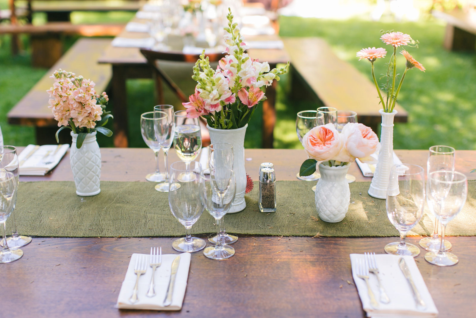 rustic table scape decor with salmon pink and light peach florals in antique white glass bud vases