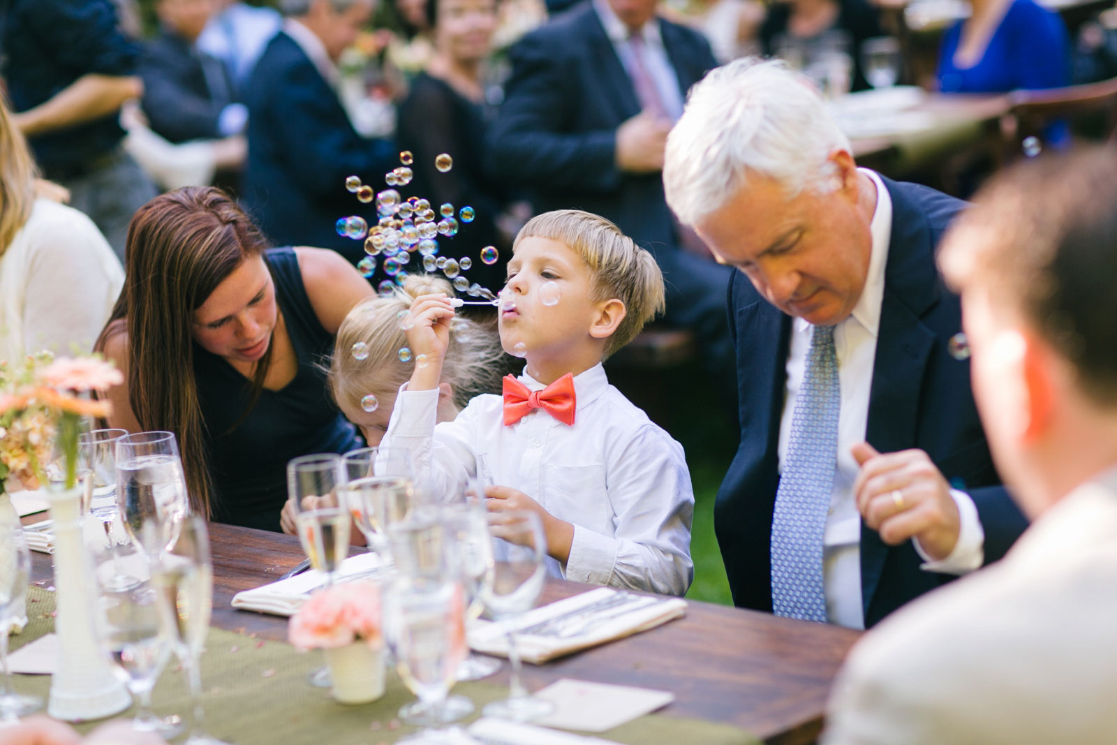 ring bearer blowing bubbles after outdoor wedding ceremony bubble exit