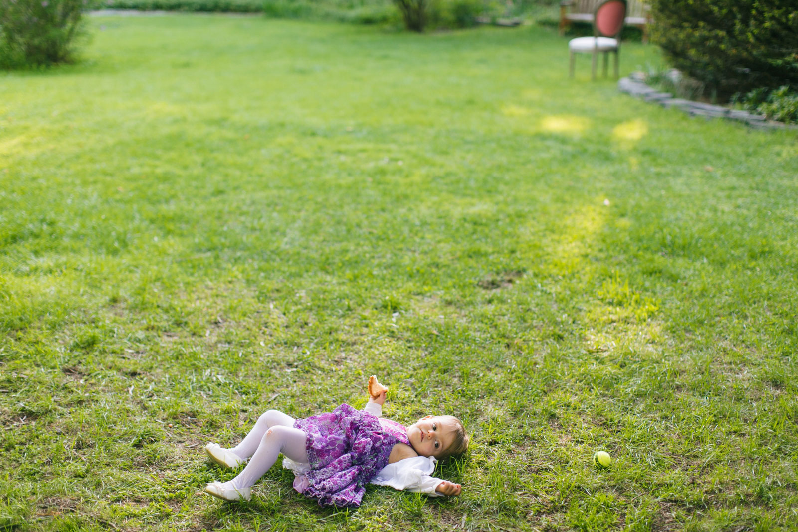 candid of toddler having fun rolling around on the grass during outdoor wedding ceremony in Boston
