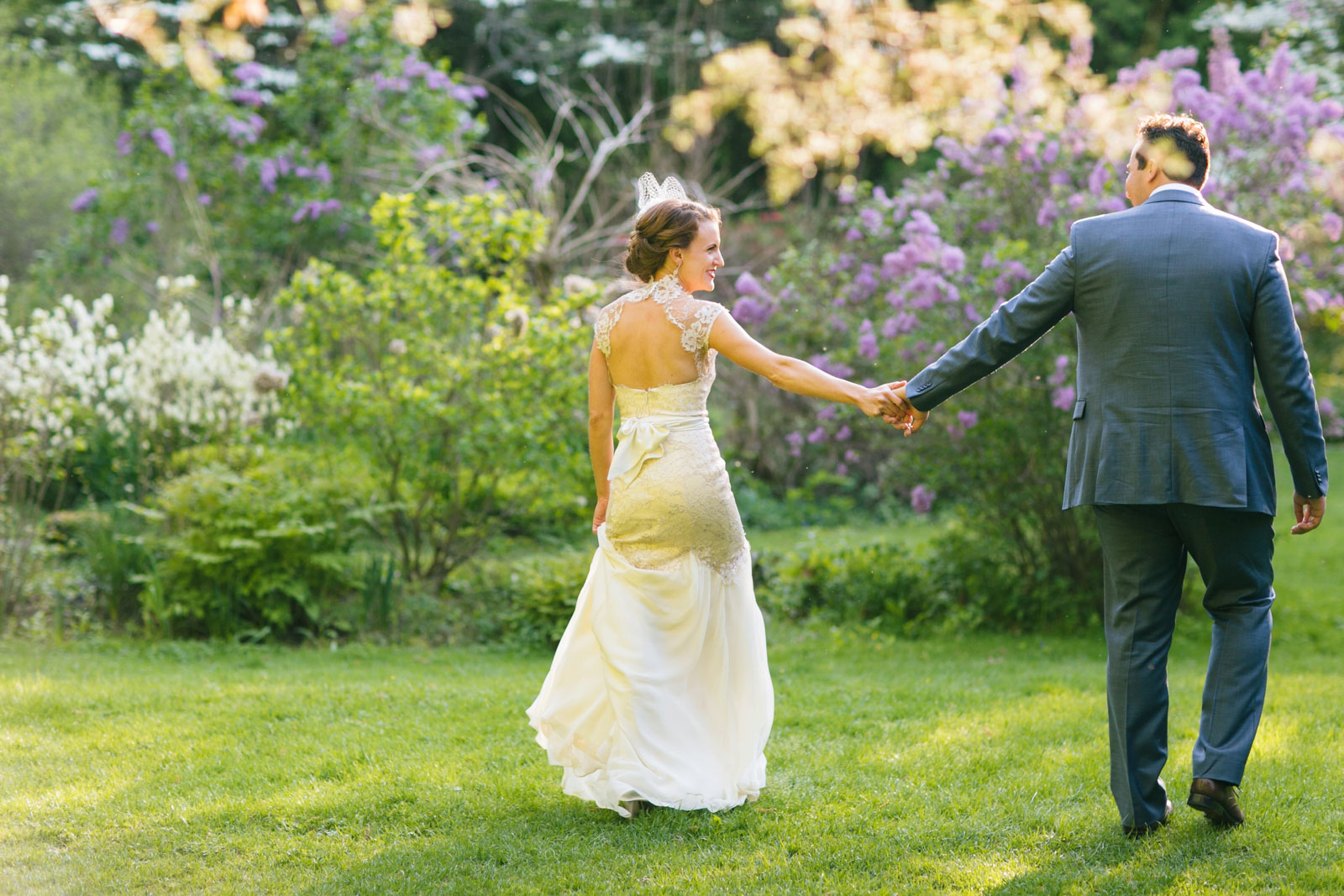 bride and groom holding hands as they walk through gardens during golden hour light