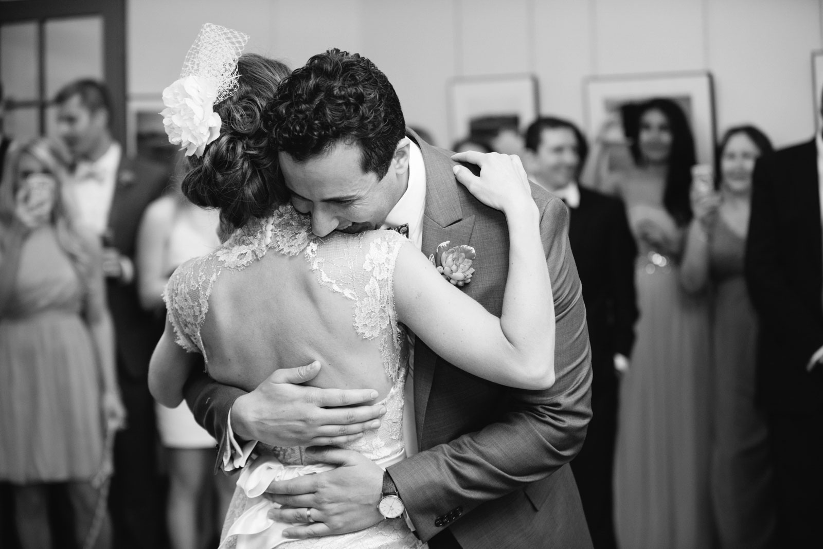 black and white intimate shot of groom hugging bride during first dance at wedding reception