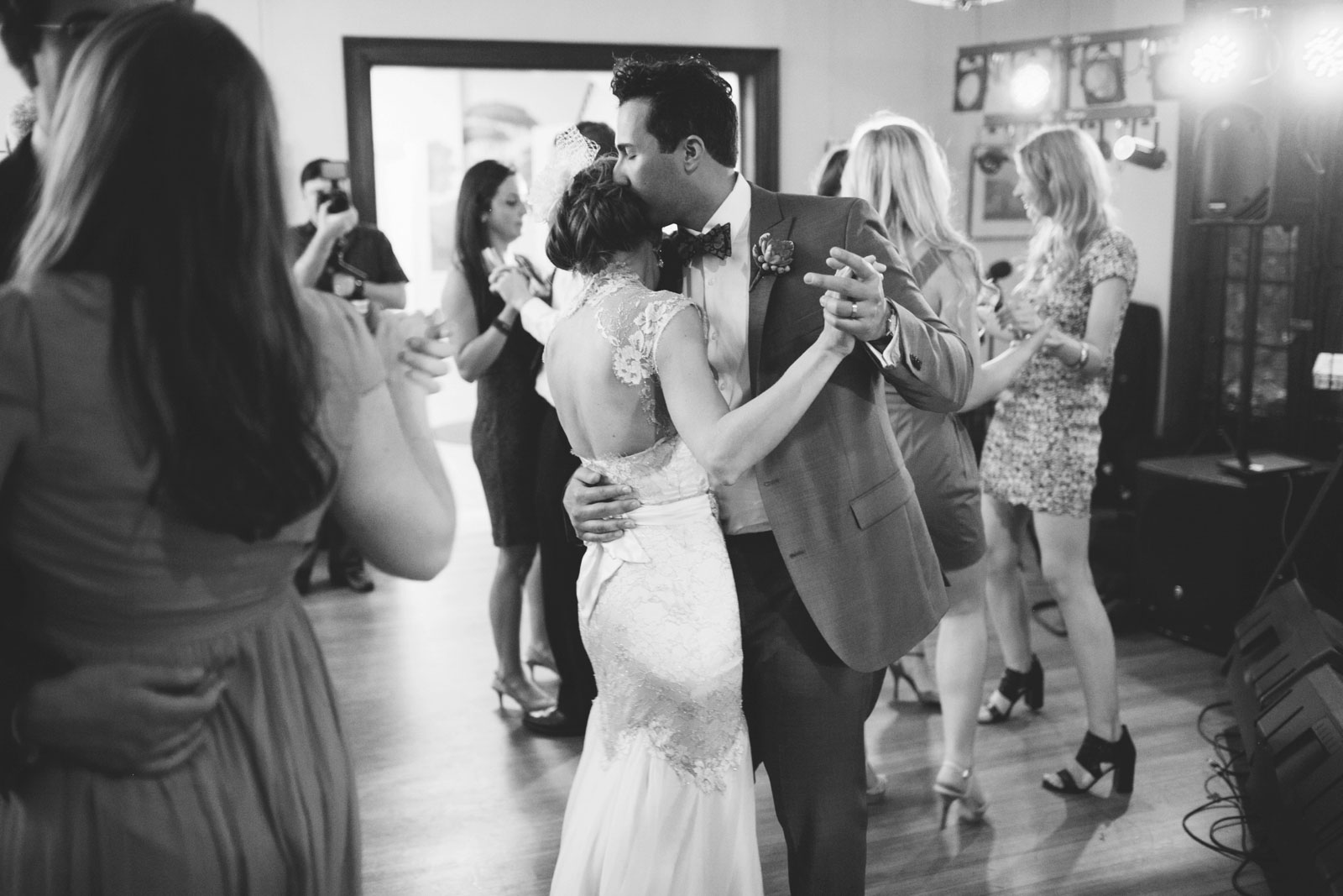 black and white intimate shot of groom hugging bride during slow song at wedding reception