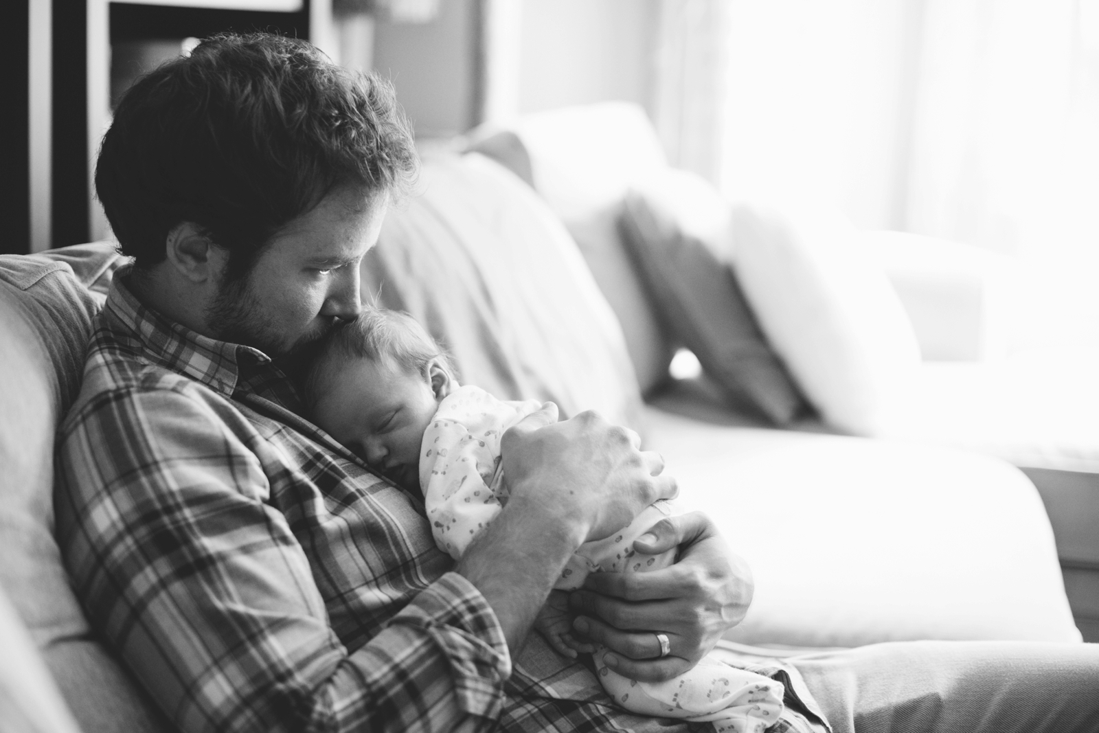 Intimate black and white newborn portrait of father holding baby on his chest, kissing baby's head