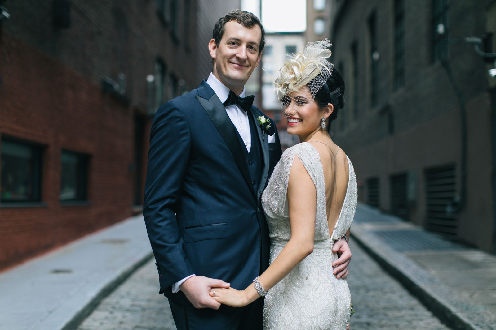 portrait of bride and groom standing in alleyway with bride showing off her backless beaded dress