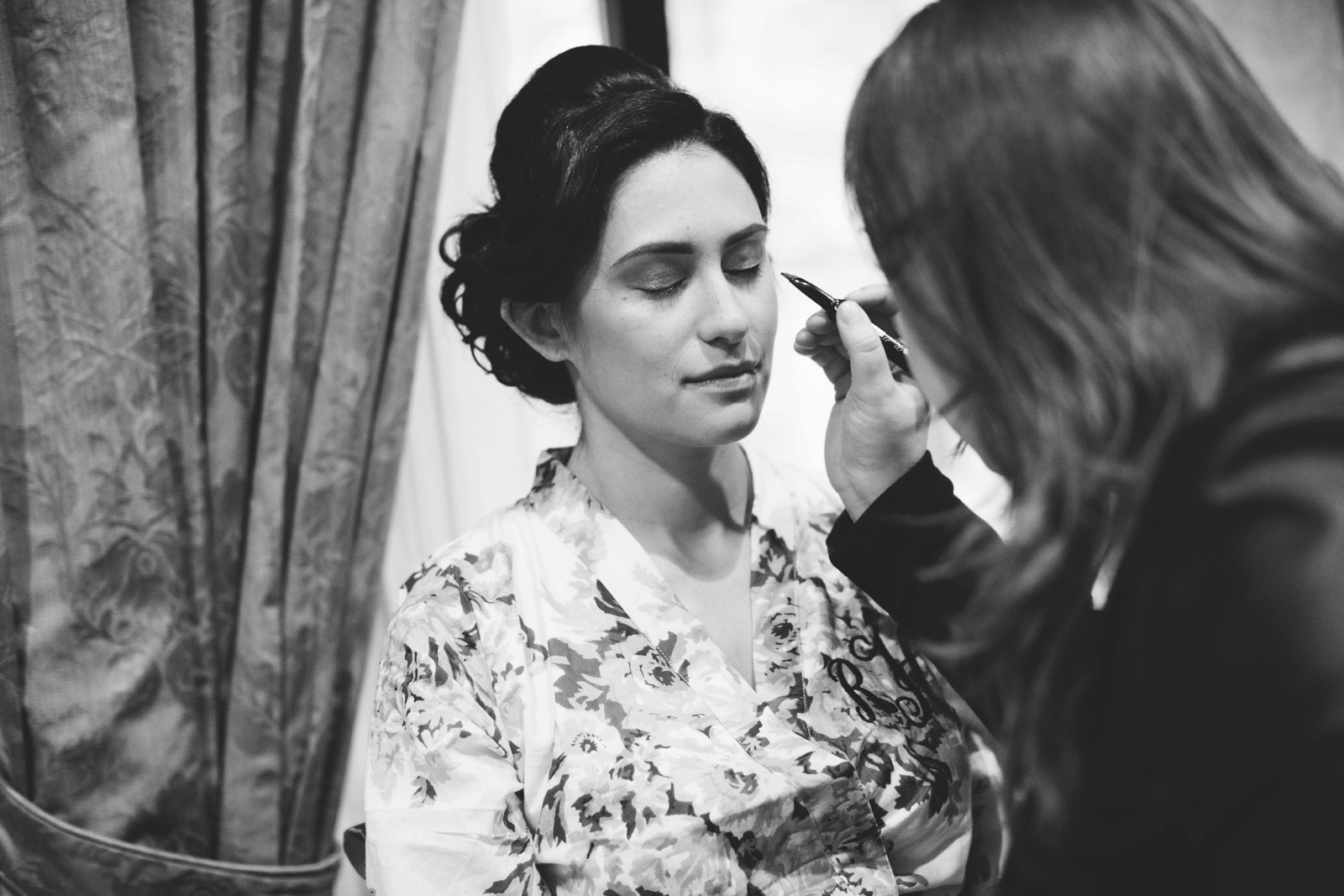black and white candid shot of bride getting her make up done in boston hotel bridal suite