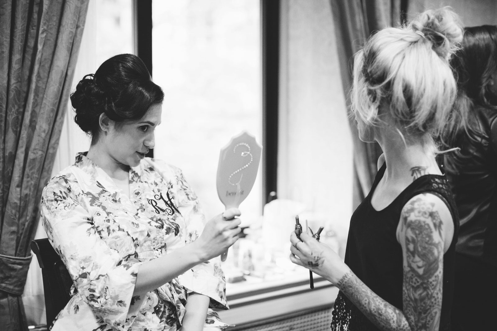 black and white shot of bride checking out her hair and make up in hand mirror