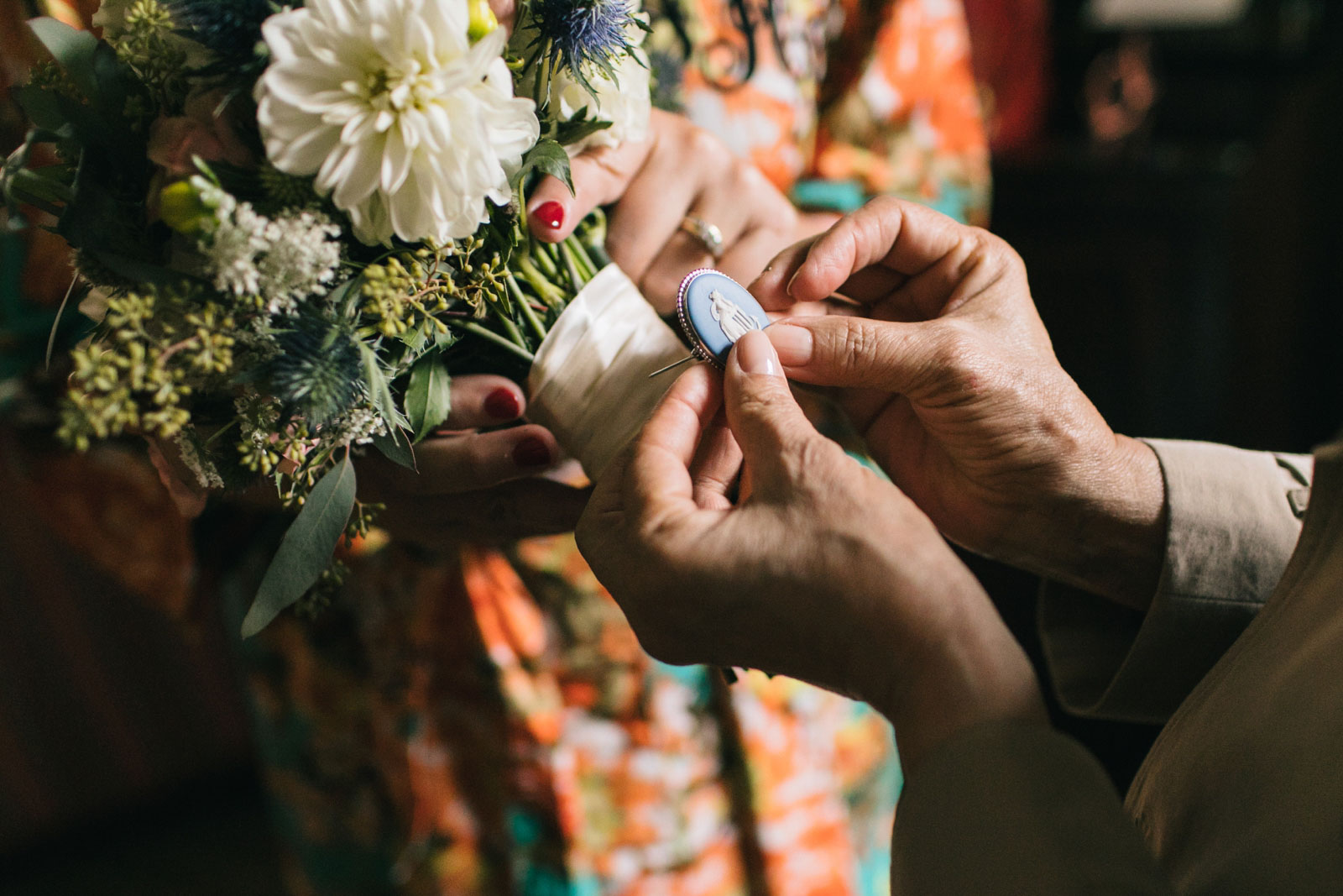 mother of the bride securing vintage wedgwood brooch heirloom onto bouquet as her