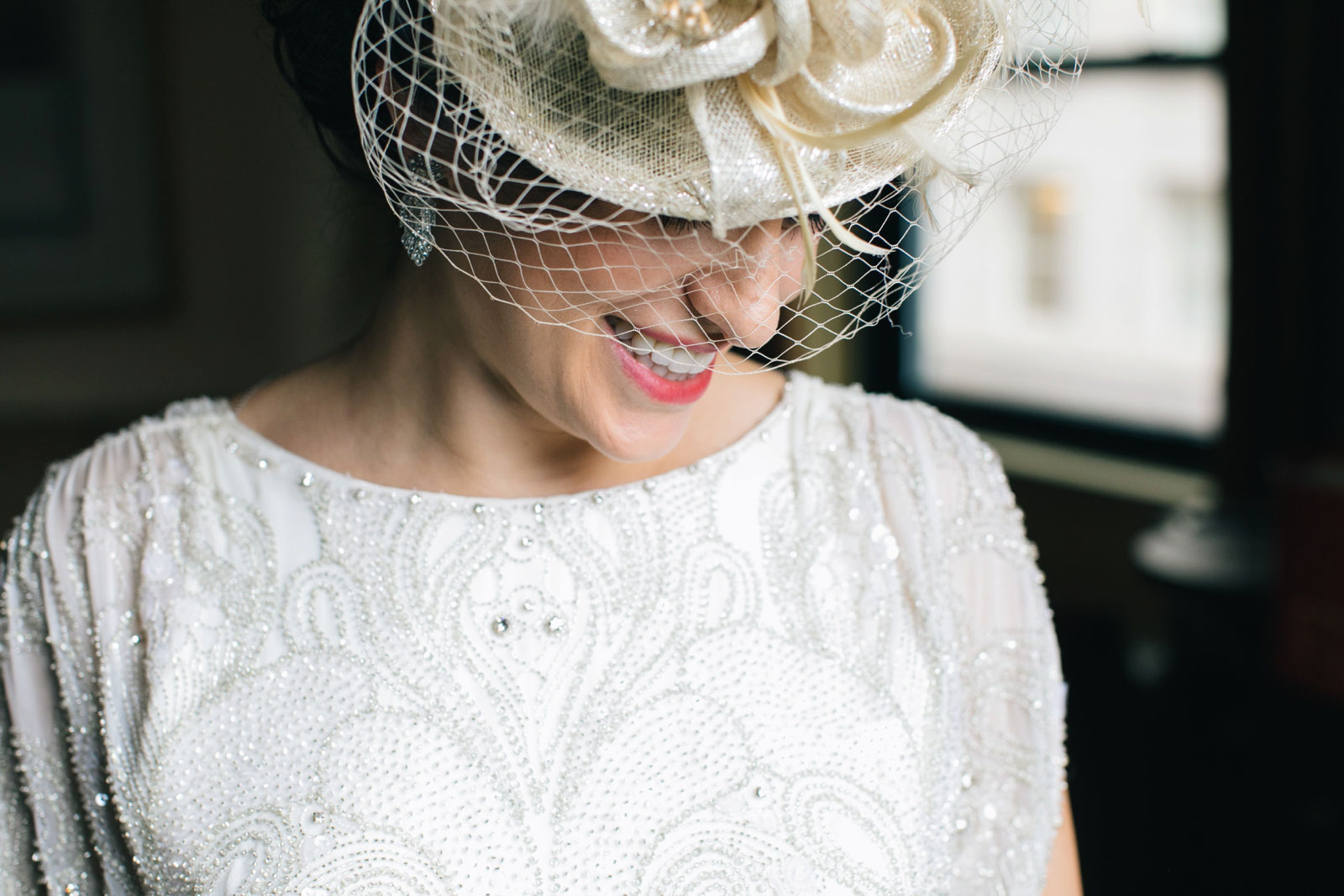 Close up of bride wearing retro fascinator with veil and vintage wedding dress with beaded detail