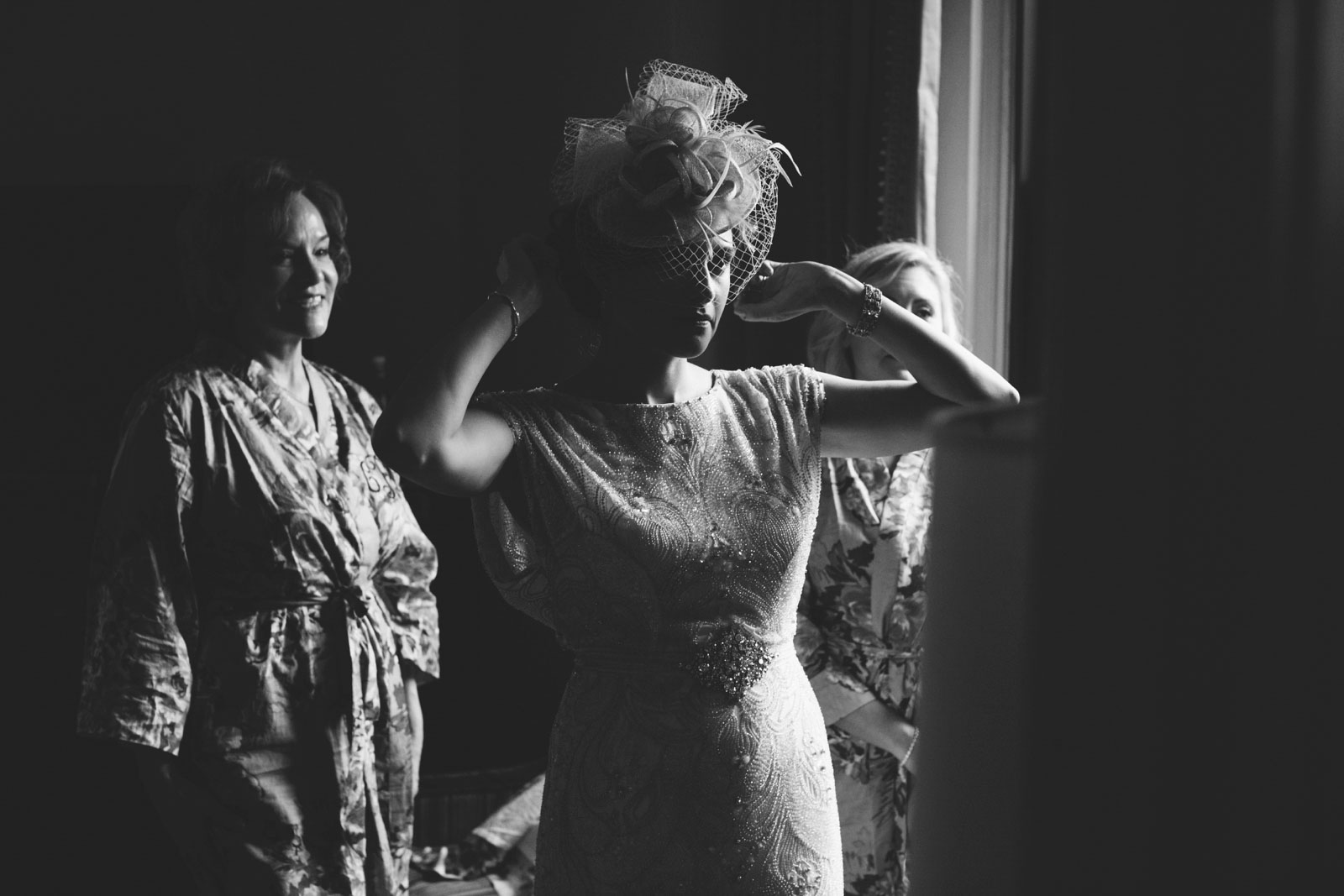 dramatic black and white shot of bride putting on fascinator with harsh shadows and natural light