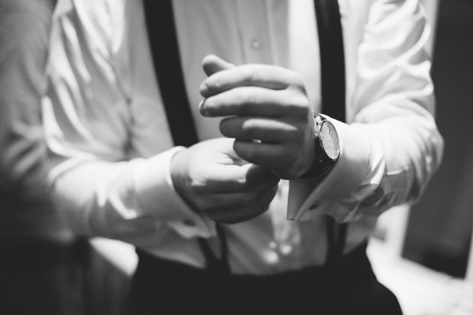 black and white close up shot of groom putting on watch while getting ready at Omni Parker House