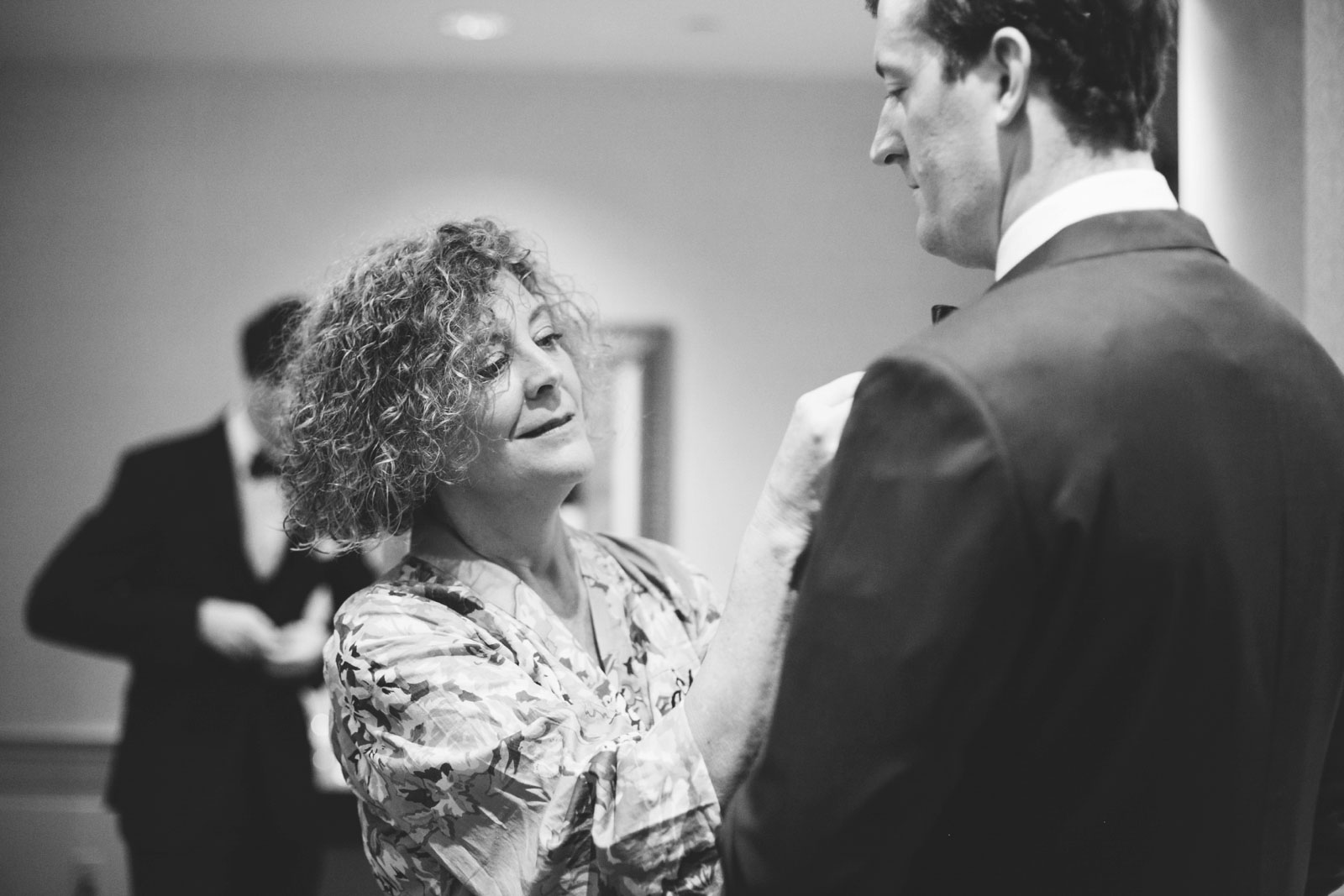 black and white shot of mother of groom helping groom with his bow tie while getting ready