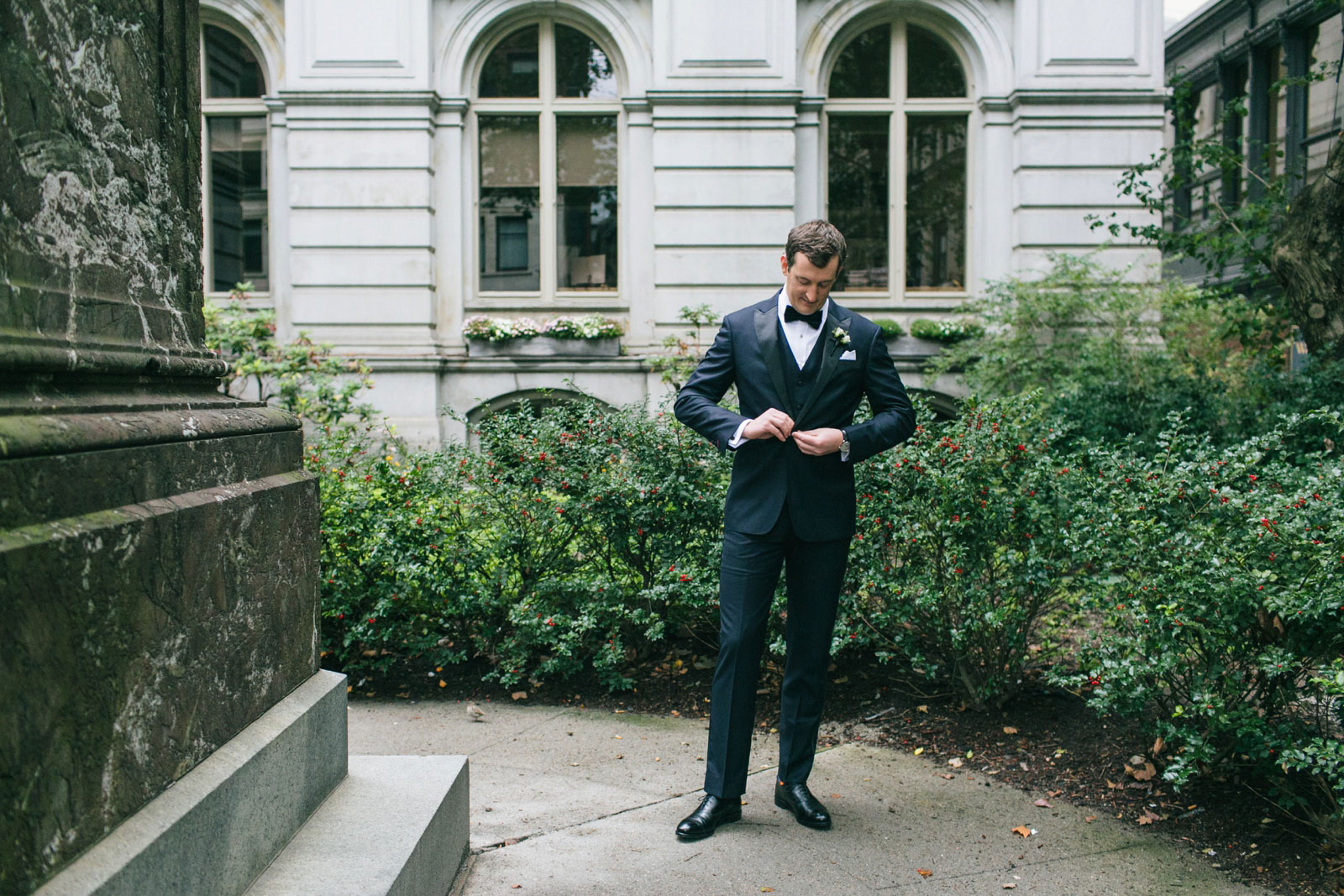 groom buttoning his jacket while he waits for bride in the gardens of old boston city hall