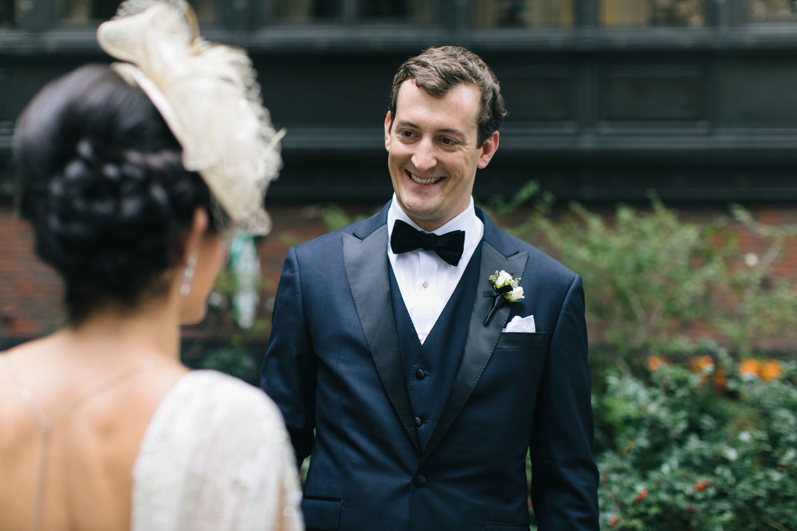 groom smiling as he sees bride for the first time during their first look at old boston city hall