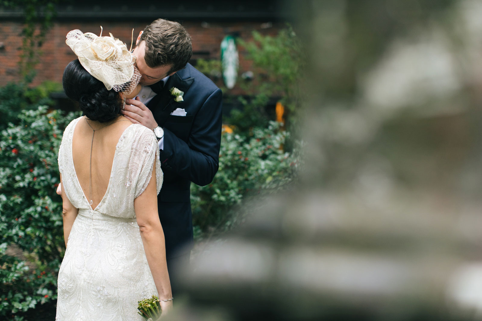 groom kisses bride romantically during their first look outside in garden at old boston city hall