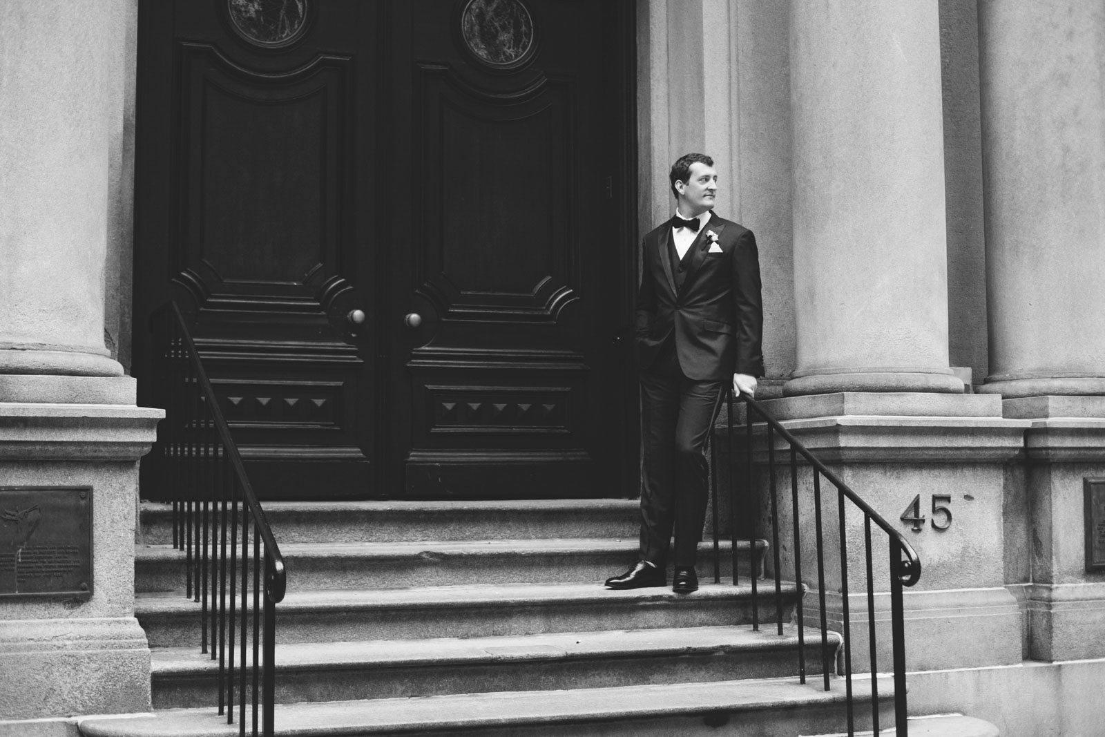 black and white shot of groom by old boston city hall with roman pillars and wrought iron railing