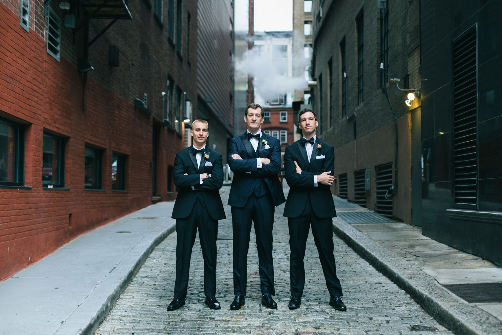 Tough-guy groomsmen portrait standing arm-crossed in alleyway with smoke in background