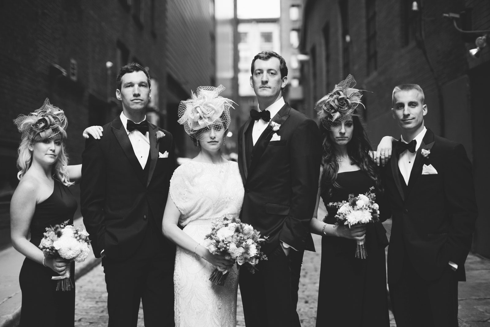 classic black and white Gatsby-inspired bridal party portrait, fascinator hats and black tie attire