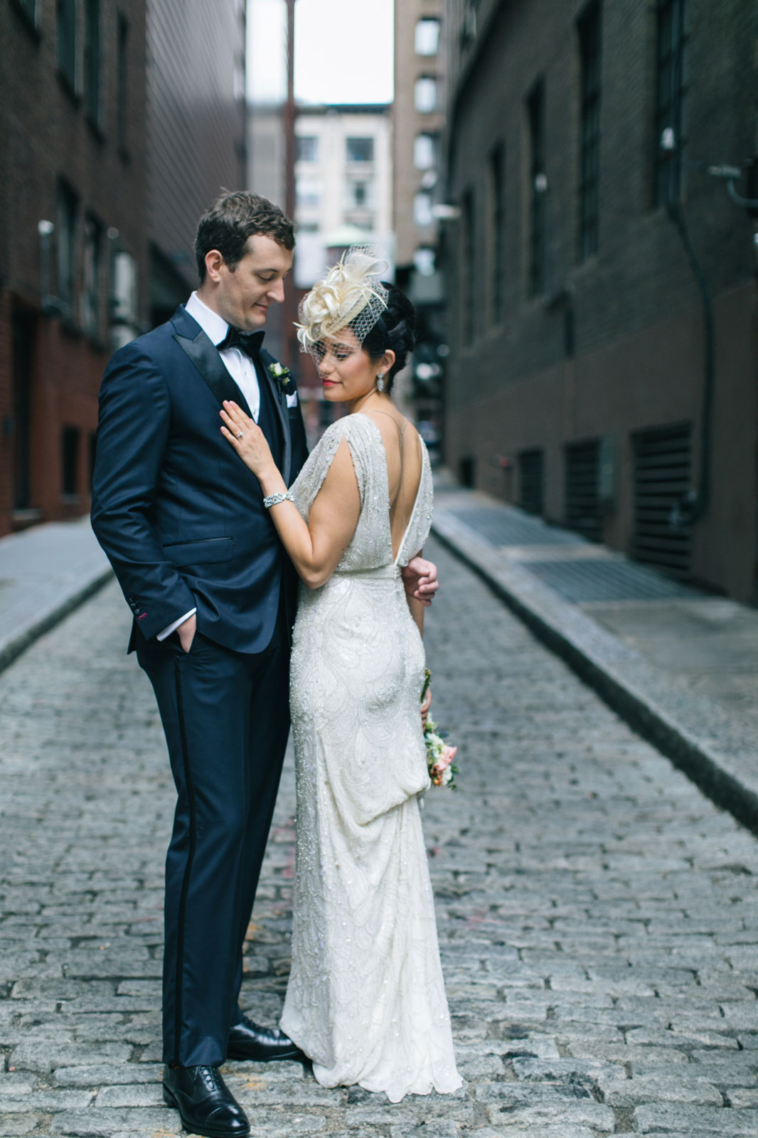 Intimate portait of bride and groom standing in alleyway, art deco inspired bridal style