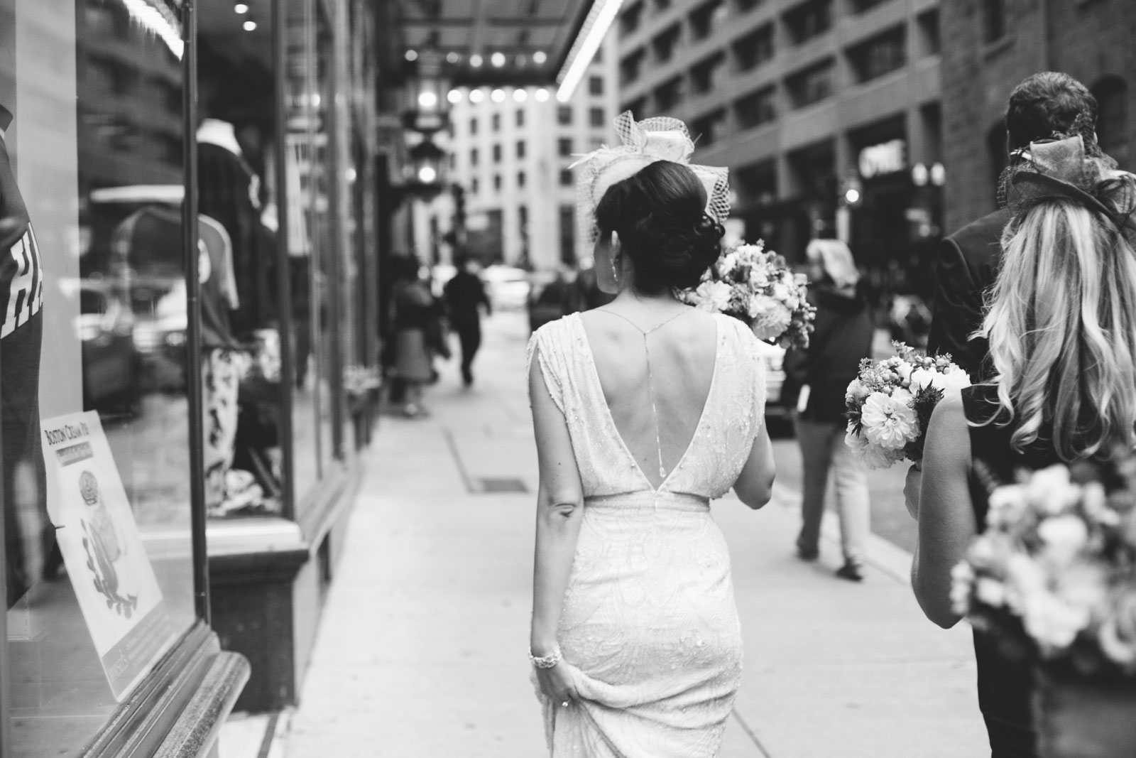 black and white shot of bride walking through Boston with backless vintage beaded wedding dress