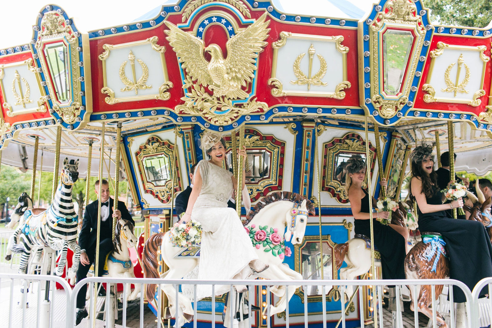 bride having fun riding on pony on carousel during bridal party portraits at boston common