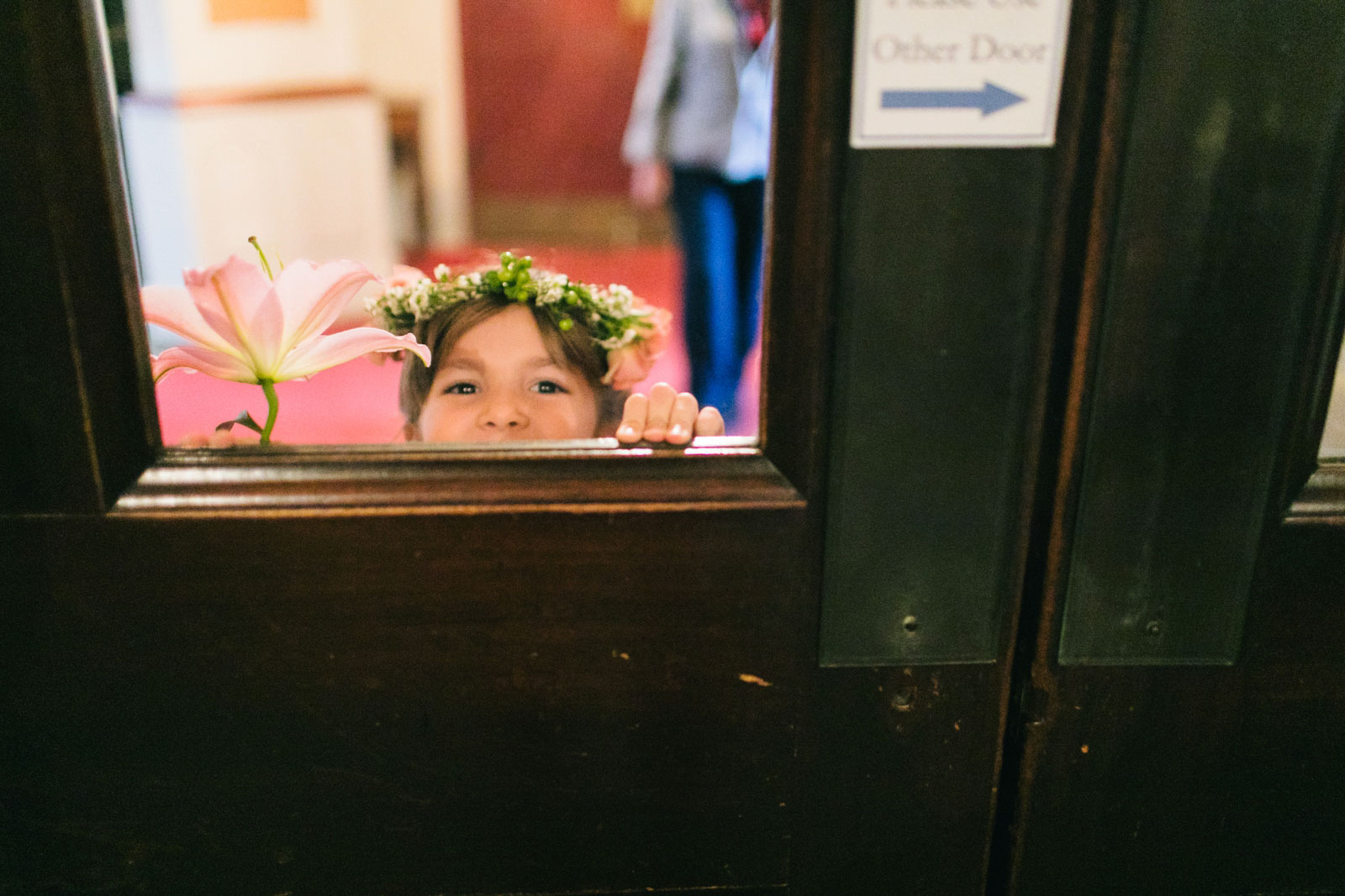 Flower girl peeks through door to ceremony space at King's chapel before wedding ceremony begins