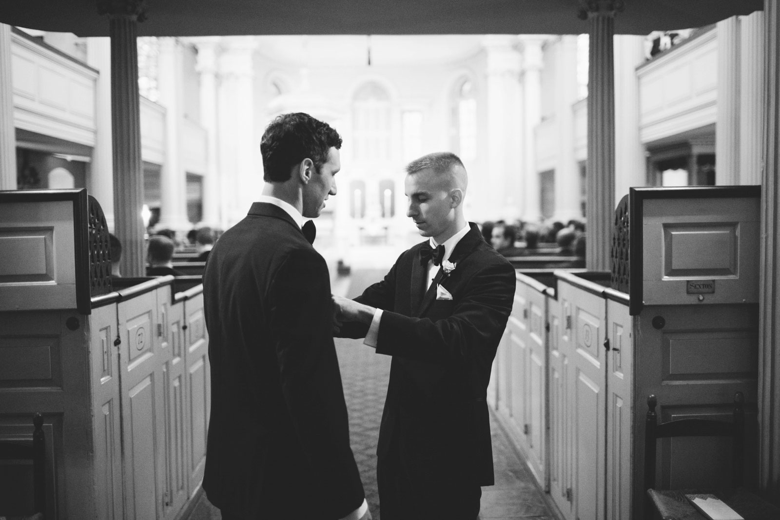 black and white shot of groomsmen fixing each other's bow ties at black tie wedding in Boston