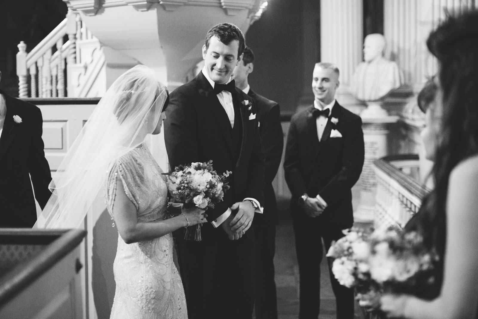 groom smiles at bride during wedding ceremony at vintage 20s era church in Boston