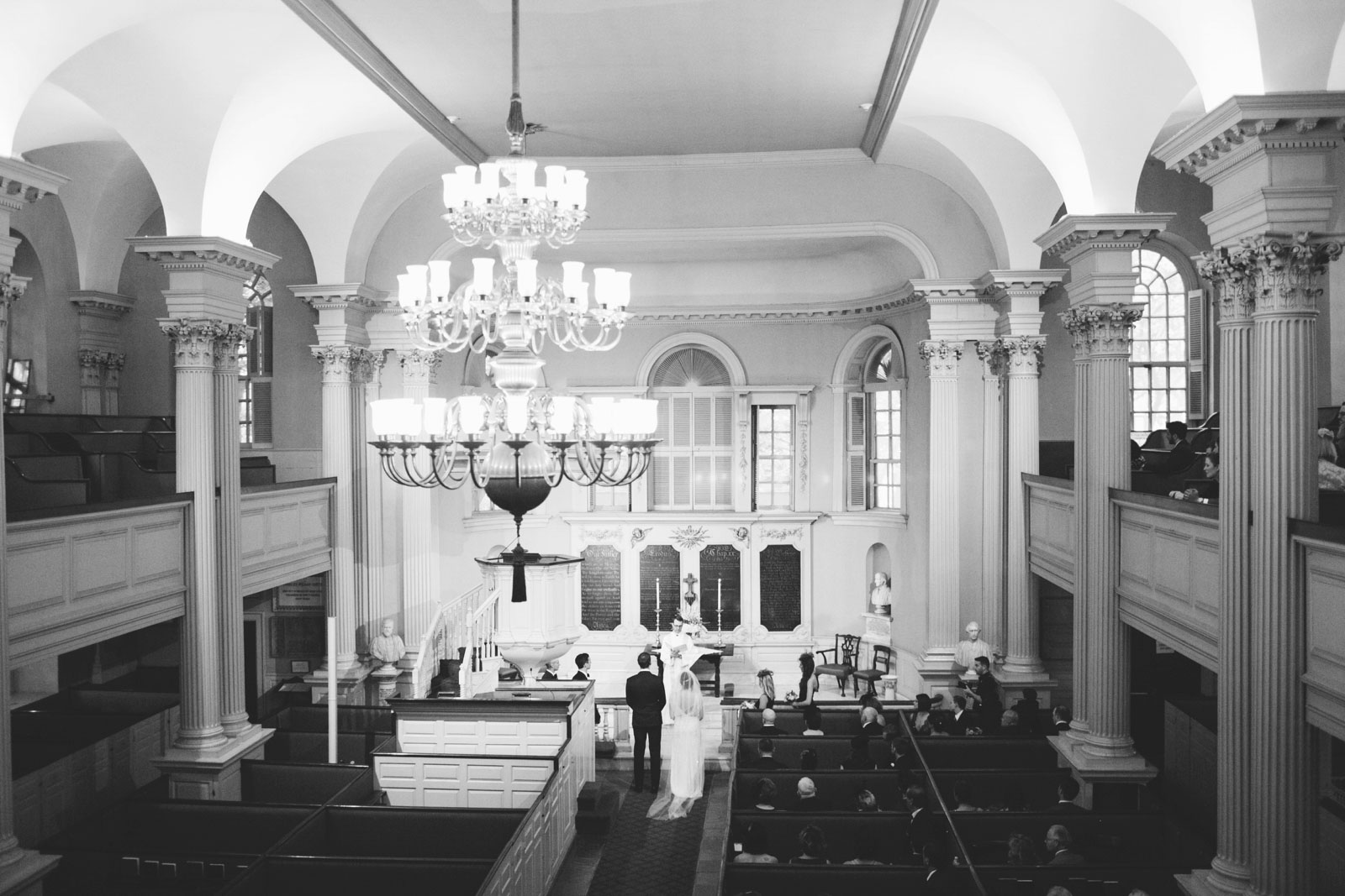 black and white shot of ceremony from above, unique boston church Roman pillars and red silk pews