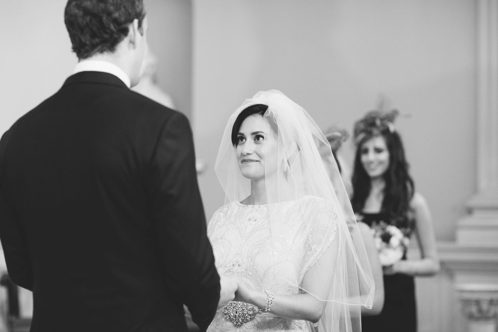 black and white shot of bride smiling up at groom during vintage-inspired wedding ceremony in Boston