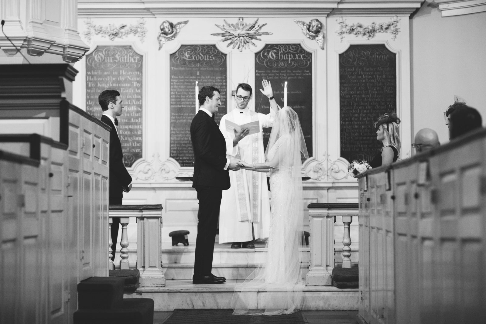 Black and white shot of bride and groom holding hands at altar during unique church wedding