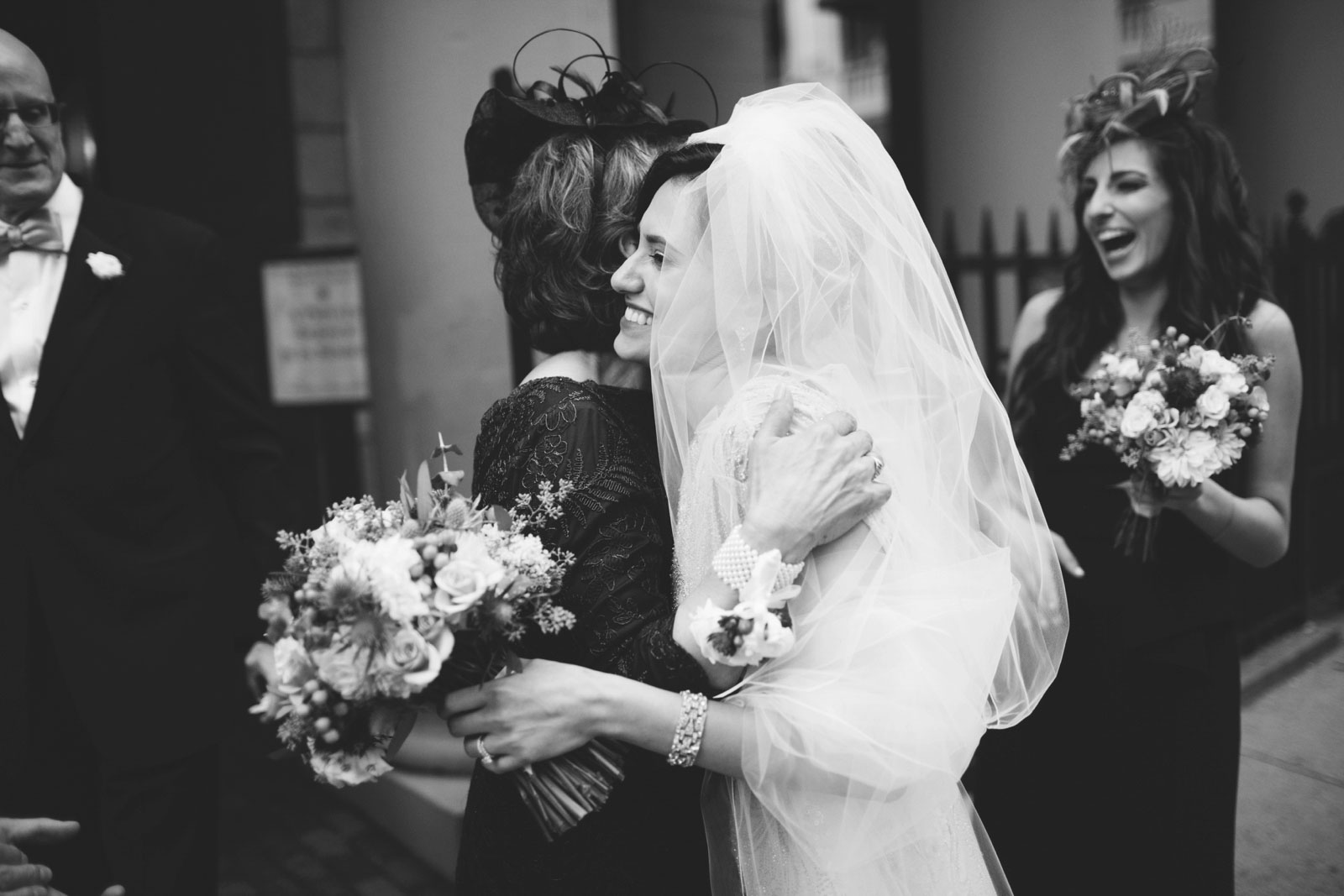 intimate candid shot of bride smiling and hugging mother of bride after wedding ceremony