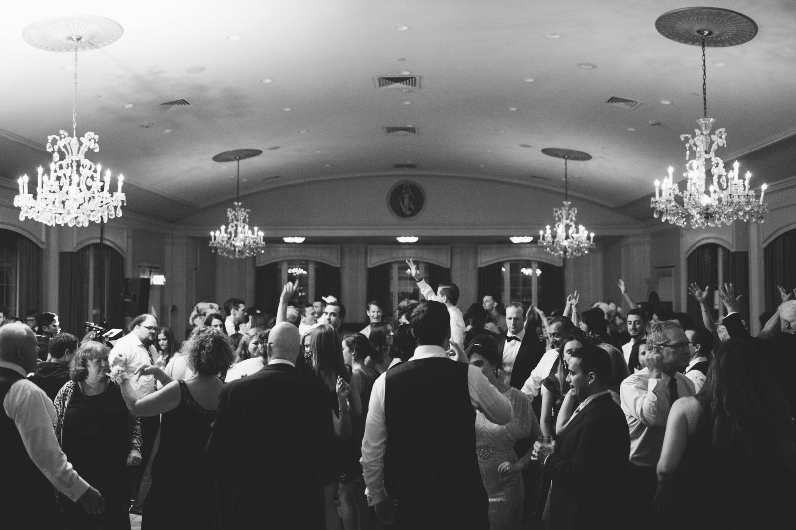 black and white shot of the crowd dancing during wedding reception with crystal chandeliers