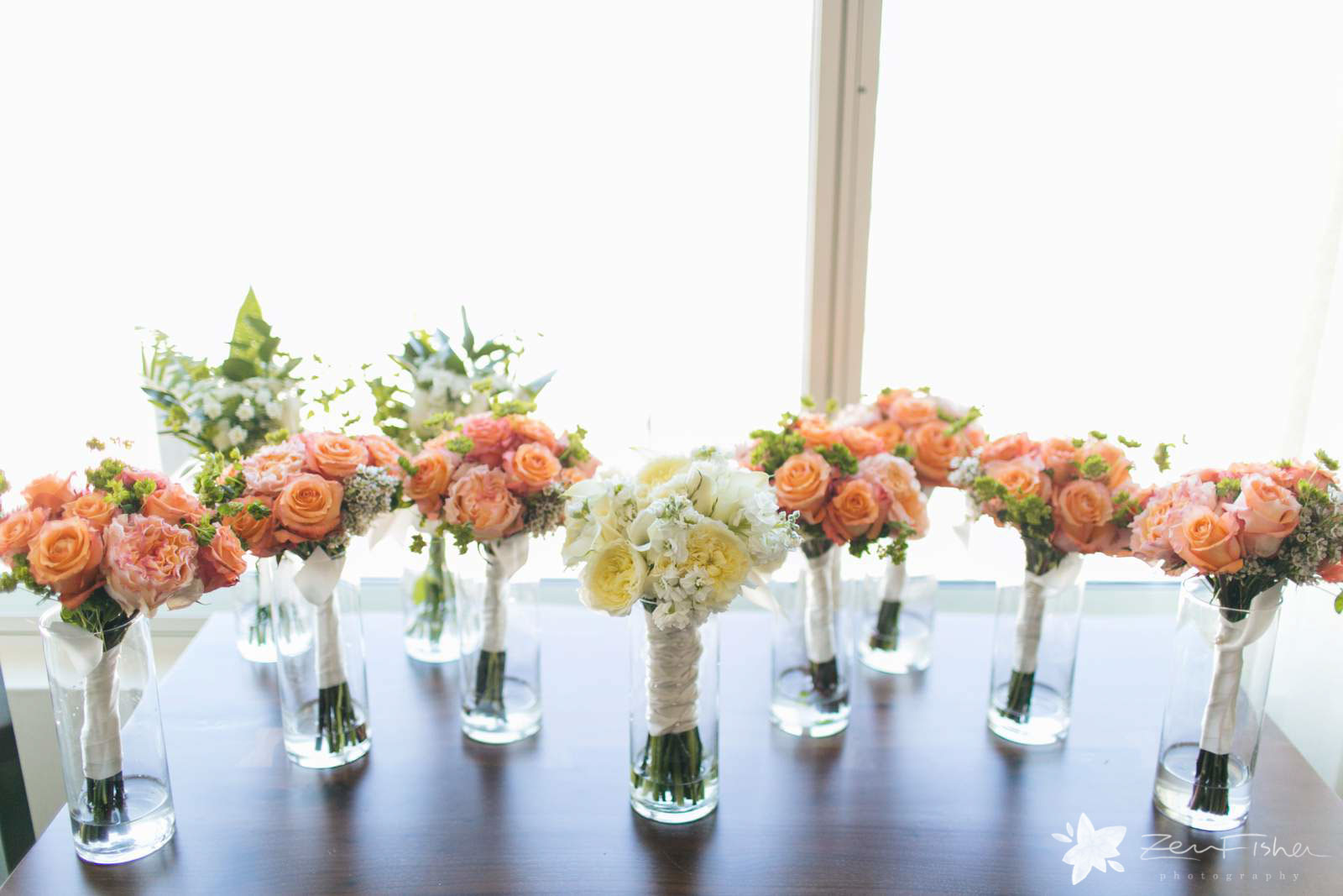 Bouquets lined up on a table in front of a window in vases, bouquet with orange and pink roses.