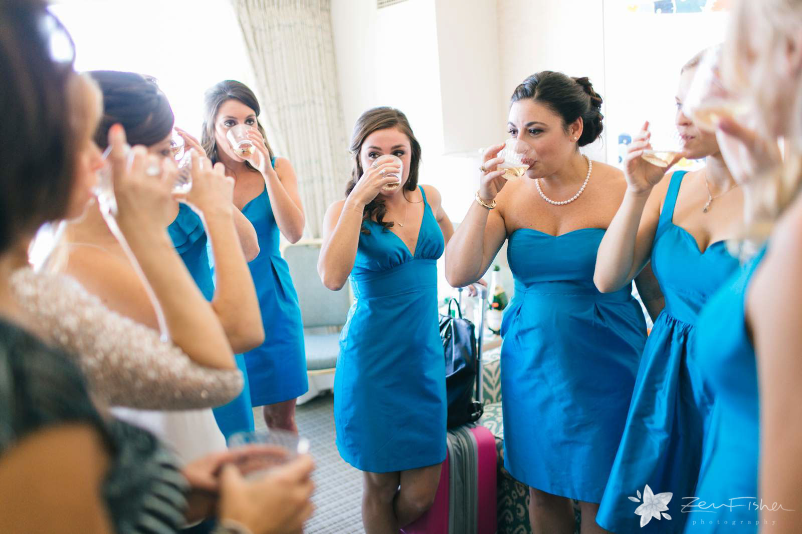 Bridesmaids sipping champagne in the hotel room while getting ready, blue bridesmaids dresses.