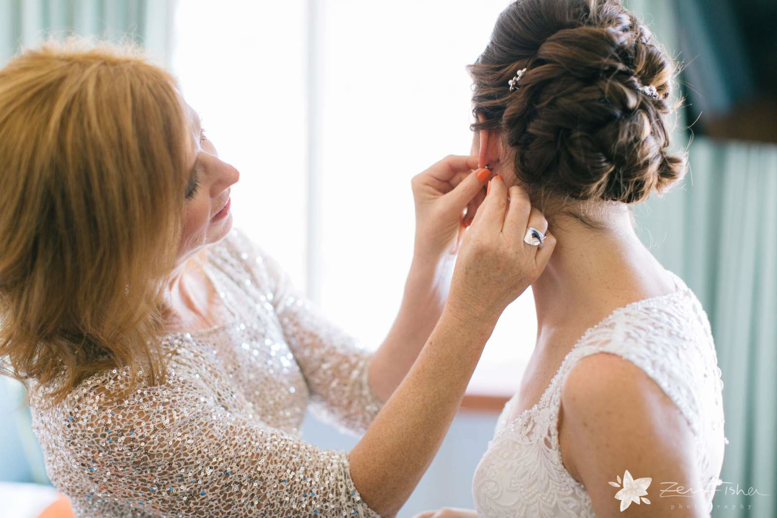 Mother of the bride putting on bride's earrings, bride getting ready in natural light from window.