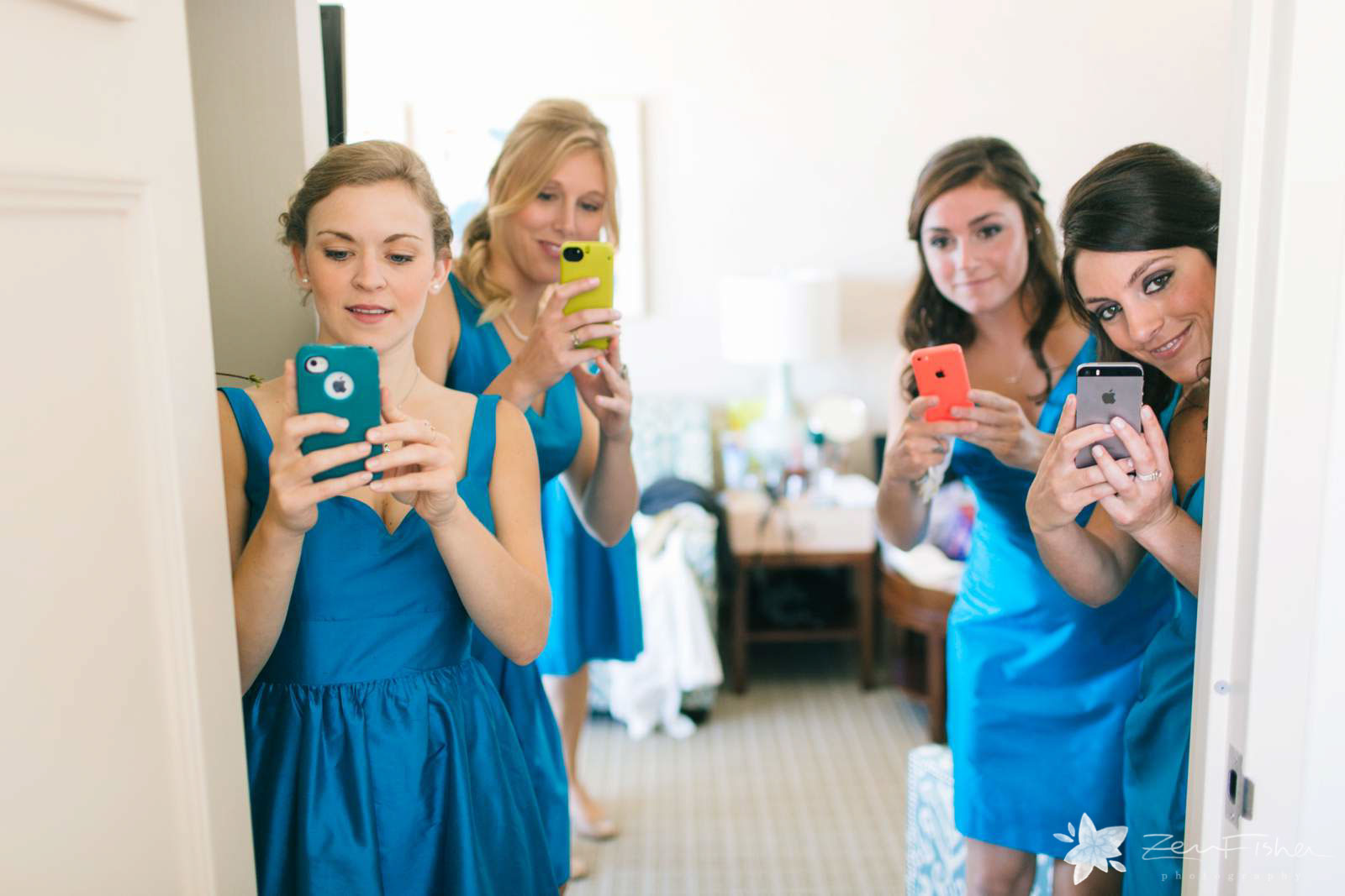 bridesmaids taking pictures with their iPhones and watching bride getting ready.