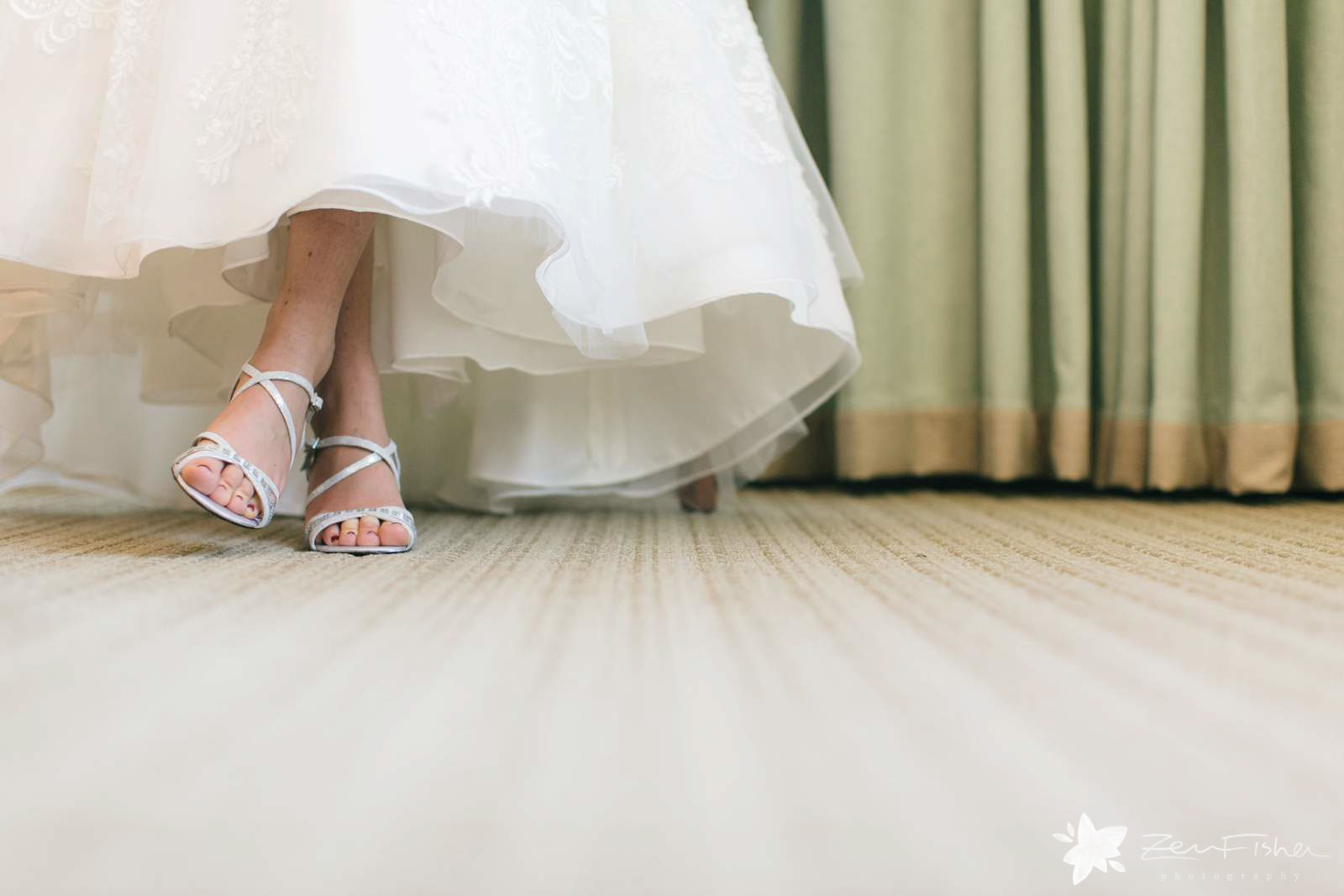 Bride's dress lifts up while she is sitting so you can see her shoes, playful moment.