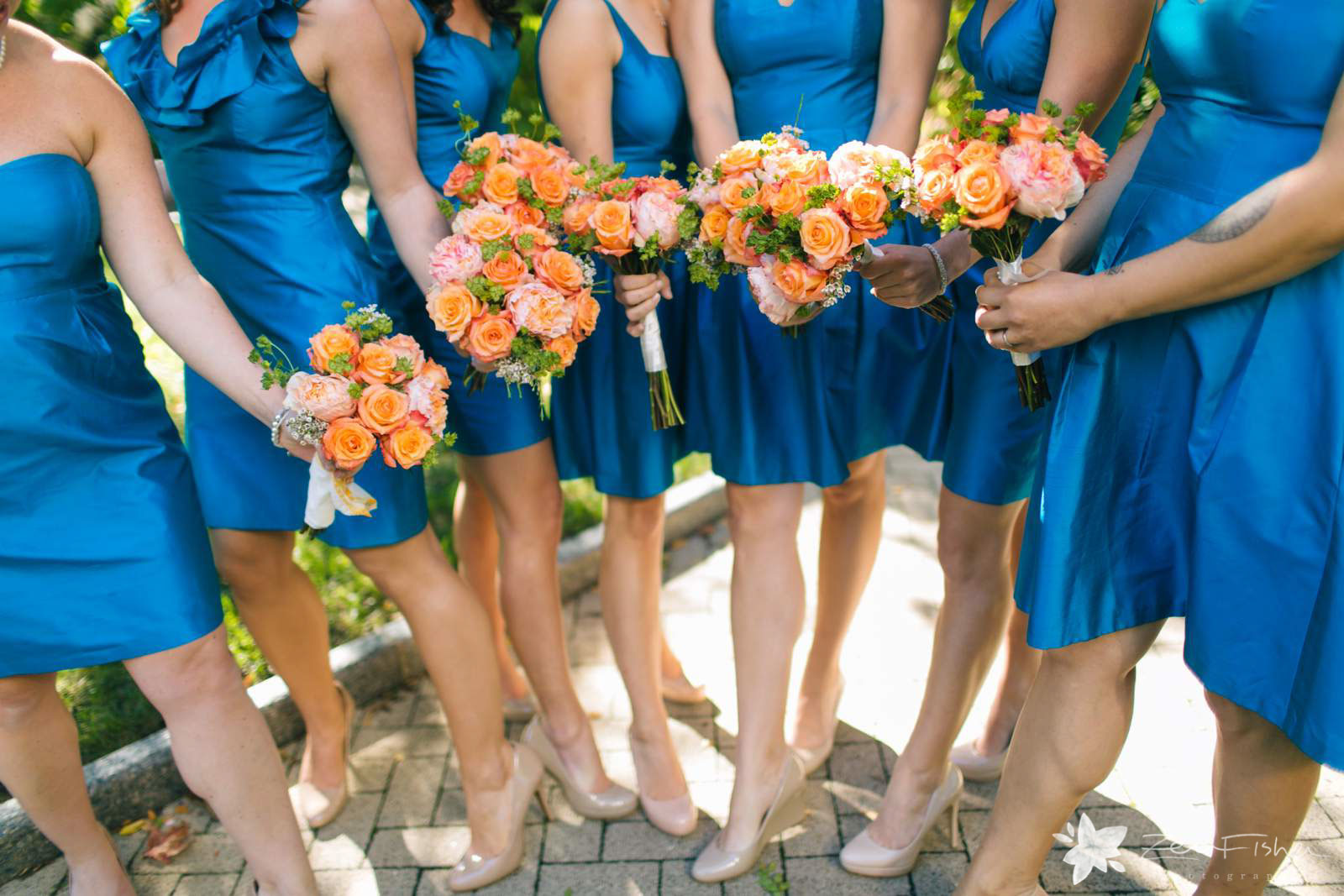 Detail of bridesmaid holding pink and orange bouquets, different styles blue bridesmaids dresses.