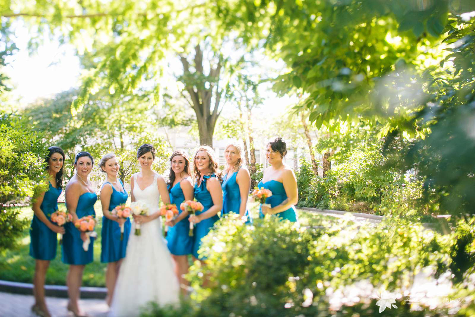 Bridal party portraits on sunny fall day in garden, branches of leaves vines cascading around them.