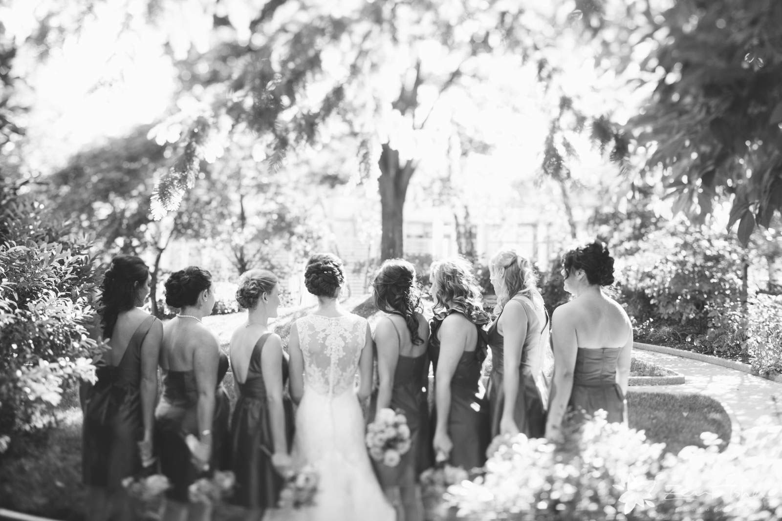 Black and white bride and bridesmaids portrait showing back of dresses and hair styles.