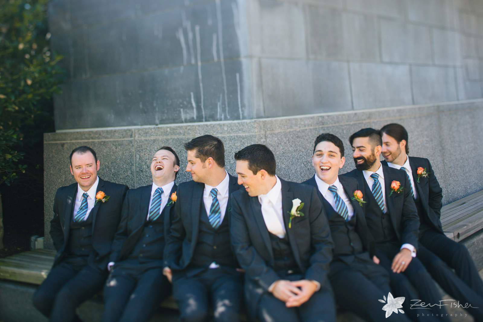 Casual groomsmen portrait, groom and groomsmen sitting outside and laughing together.