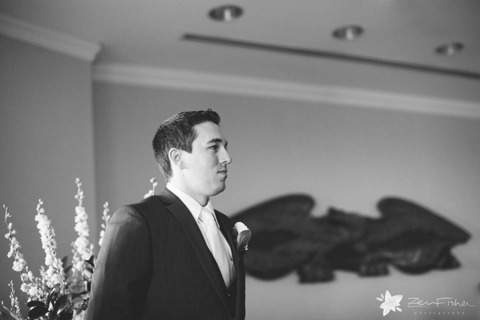 Groom stands at altar waiting in anticipation for bride to come down the aisle, black and white.