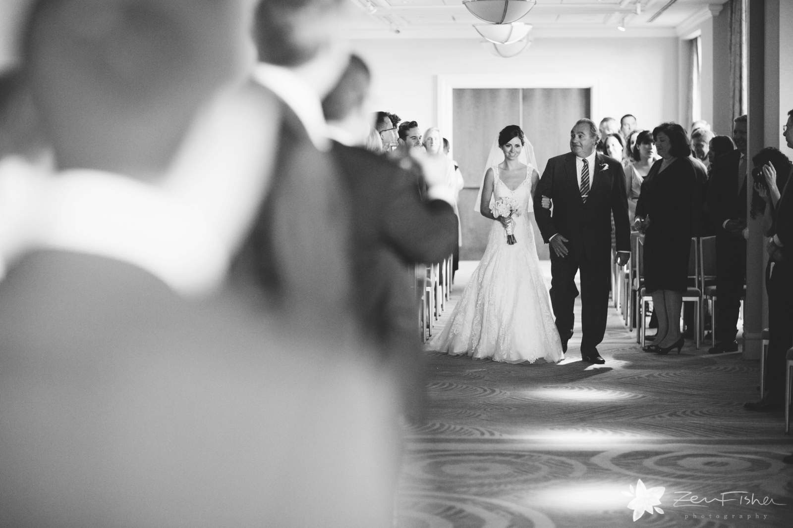 Bride walking down the aisle with her father, black and white, natural light