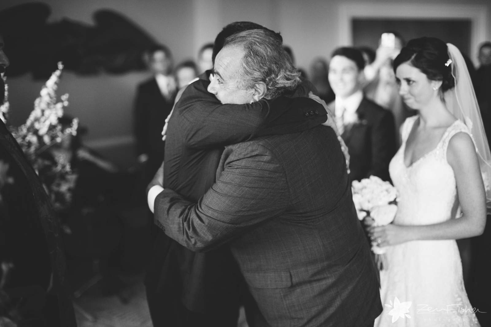 Father gives away the bride, bride watches her father give groom a big bear hug.