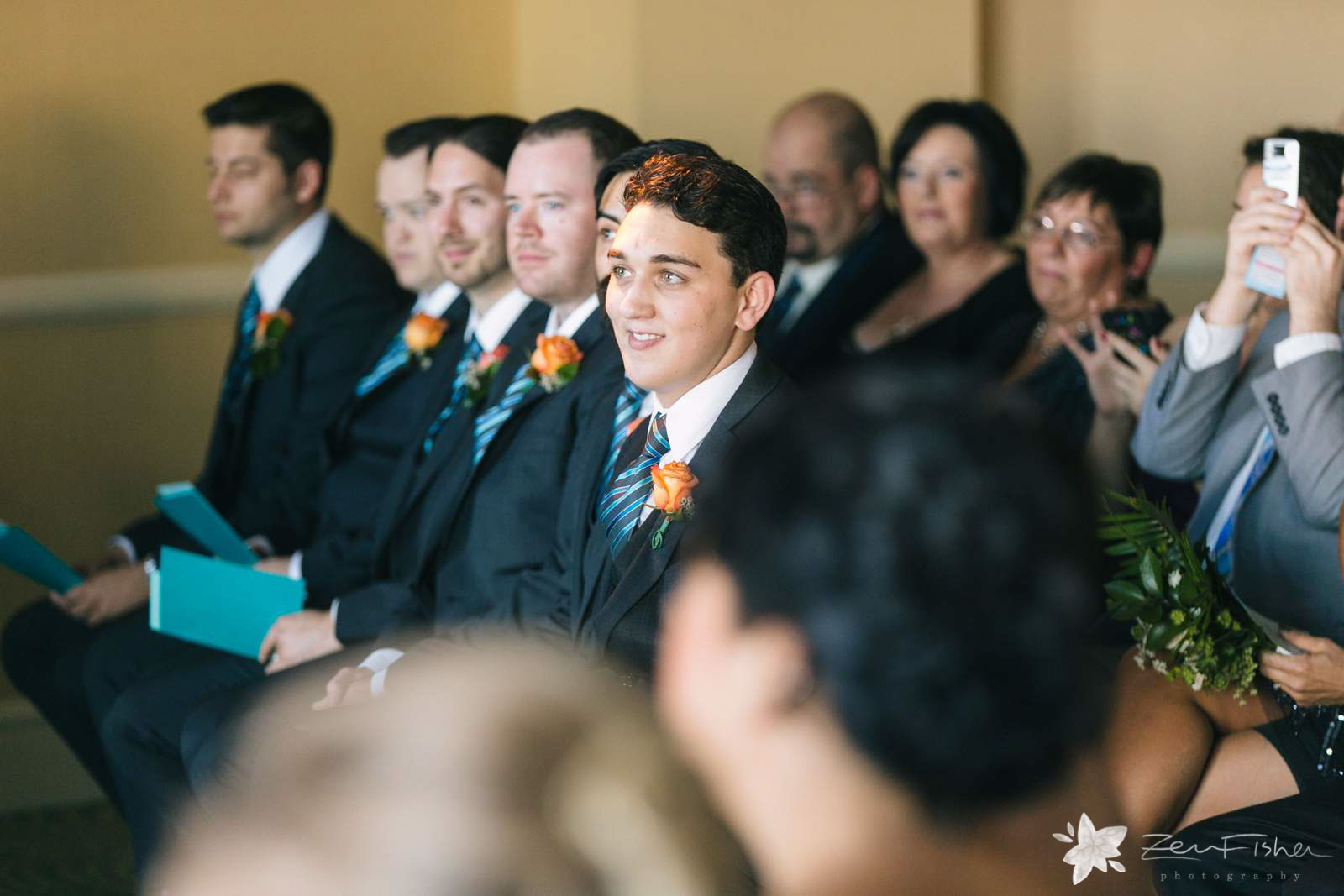 Groom's brother smiling and watching the ceremony from the front row. Boutinerre with orange rose