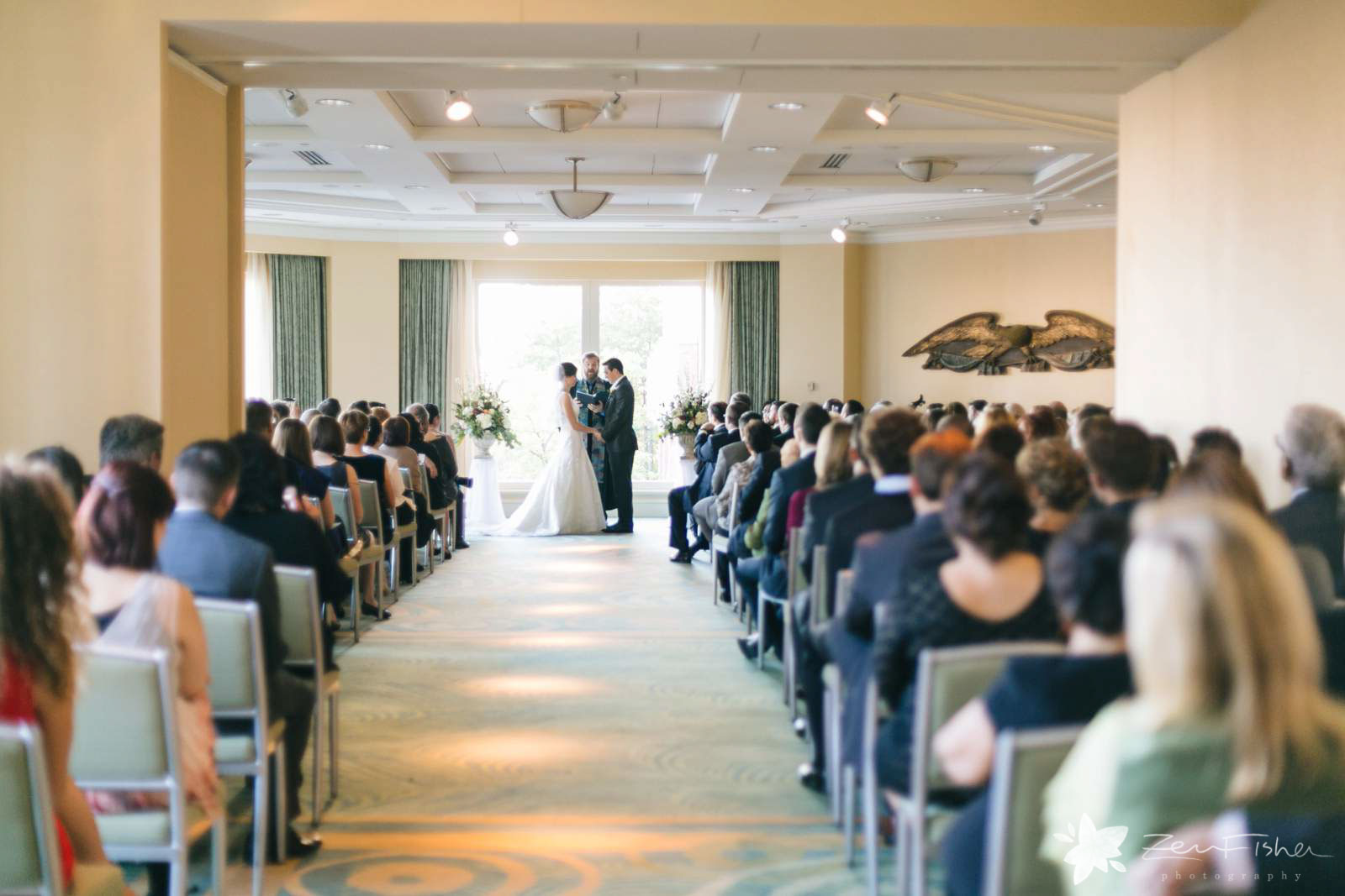 Wide shot of ceremony from the back, bride and groom standing in front of window facing each other